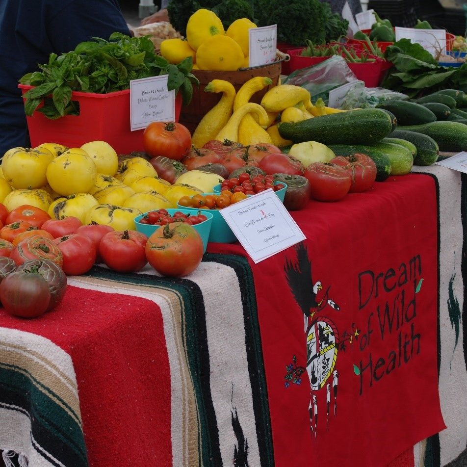 DWH farmers market booth featuring an assortment of mid-summer veggies.